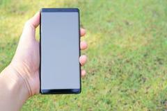 Mano femenina que lleva a cabo el negro del smartphone foto de archivo libre de regalías
