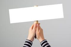 Mano femenina que lleva a cabo la muestra en blanco de la bandera de la maqueta como espacio de la copia foto de archivo libre de regalías