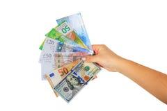 Mano femenina que lleva a cabo los dólares de papel de los billetes de banco, euro, el franco suizo y la libra británica Fotos de archivo libres de regalías