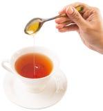 Mano femenina que mezcla a Honey With Tea V Imagen de archivo libre de regalías