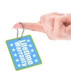 Mano femenina que muestra la etiqueta de la garantía Foto de archivo libre de regalías