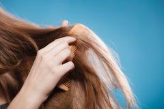 Mano femenina que peina el pelo con el peine de madera Fotos de archivo
