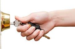 Mano femenina que pone llave de la casa en la cerradura de puerta principal aislada Imagen de archivo