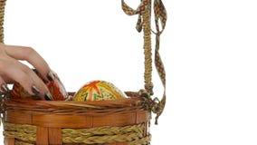 Mano femenina que pone los huevos de Pascua en la cesta metrajes