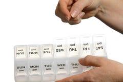 Mano femenina que pone píldoras en dispensador programado Foto de archivo