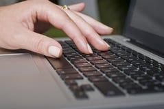 Mano femenina que pulsa en un teclado de la computadora portátil Imágenes de archivo libres de regalías