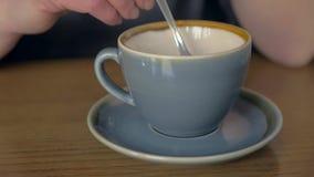 Mano femenina que revuelve el café en una taza almacen de metraje de vídeo