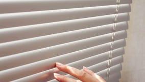 Mano femenina que separa los listones de las persianas con un finger para ver a través almacen de video