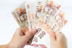 Mano femenina que sostiene billetes de banco checos Fotografía de archivo libre de regalías