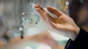 Mano femenina que sostiene el colgante del diamante, surtido de la joyería en alameda de compras de lujo almacen de video