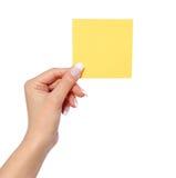 Mano femenina que sostiene el papel de nota, aislado en la etiqueta engomada blanca, amarilla Foto de archivo