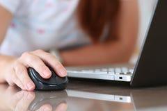 Mano femenina que sostiene el ratón de la radio del ordenador Imagenes de archivo