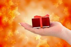 Mano femenina que sostiene el regalo rojo en fondo estrellado Imagen de archivo