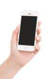 Mano femenina que sostiene el teléfono elegante móvil blanco moderno con s en blanco Fotografía de archivo