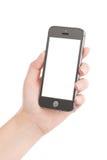 Mano femenina que sostiene el teléfono elegante móvil negro moderno con s en blanco Fotos de archivo