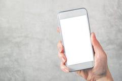 Mano femenina que sostiene el teléfono móvil con mofa del espacio en blanco encima de la pantalla imagenes de archivo