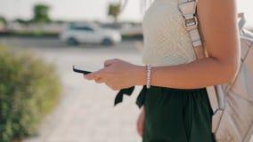 Mano femenina que sostiene el teléfono móvil en el fondo de la ciudad vieja en el verano, primer almacen de video