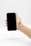 Mano femenina que sostiene el teléfono móvil negro con la pantalla negra imagen de archivo