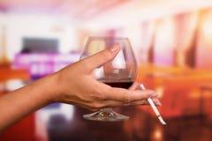 Mano femenina que sostiene el vidrio del whisky y del cigarrillo en fondo el restaurante Fotos de archivo libres de regalías