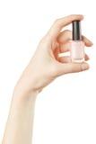 Mano femenina que sostiene la botella rosada del esmalte de uñas foto de archivo libre de regalías