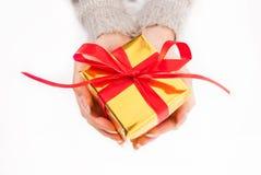 Mano femenina que sostiene la caja de oro presente con el arco rojo en el fondo blanco Foto de archivo libre de regalías