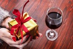 Mano femenina que sostiene la caja de oro presente con el arco rojo en fondo y copa de vino de madera en la tabla Imagen de archivo libre de regalías