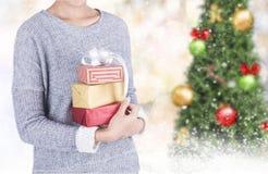 Mano femenina que sostiene la caja de regalo con la luz del bokeh del árbol de navidad Foto de archivo libre de regalías