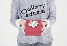 Mano femenina que sostiene la caja de regalo roja con Feliz Navidad Imágenes de archivo libres de regalías