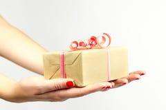 Mano femenina que sostiene la caja de regalo roja y amarilla con un arco aislado en el fondo blanco Foto de archivo