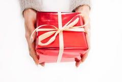 Mano femenina que sostiene la caja roja presente con el arco blanco Foto de archivo libre de regalías