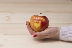 Mano femenina que sostiene la manzana con te amo la impresión Fotografía de archivo libre de regalías