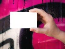Mano femenina que sostiene la tarjeta de visita blanca en blanco Fotografía de archivo