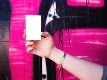 Mano femenina que sostiene la tarjeta de visita blanca en blanco Imágenes de archivo libres de regalías