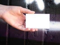 Mano femenina que sostiene la tarjeta de visita blanca en blanco Foto de archivo libre de regalías