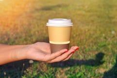 Mano femenina que sostiene la taza de bebida caliente outdoor imagen de archivo