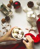 Mano femenina que sostiene la taza de chocolate caliente con la melcocha Fotografía de archivo libre de regalías