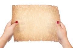 Mano femenina que sostiene la voluta de papel vieja en blanco aislada en el fondo blanco Fotos de archivo