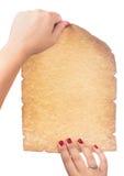 Mano femenina que sostiene la voluta vieja en blanco del papel en blanco aislada en el fondo blanco Imagenes de archivo