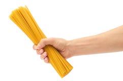 Mano femenina que sostiene los espaguetis crudos Aislado en el fondo blanco Fotos de archivo libres de regalías