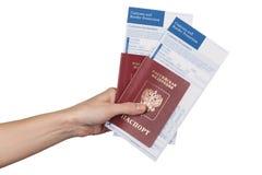 Mano femenina que sostiene los pasaportes rusos del viaje Imagenes de archivo