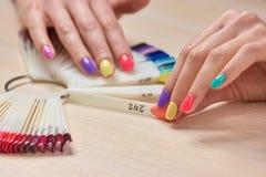 Mano femenina que sostiene muestras de los colores de los clavos Imagen de archivo libre de regalías