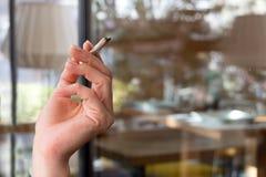 Mano femenina que sostiene un cigarrillo Imagen de archivo