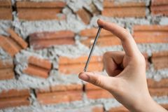 Mano femenina que sostiene un clavo de la construcción con backgrou de la pared de ladrillo imagen de archivo