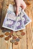Mano femenina que sostiene un dinero británico imagenes de archivo