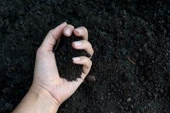 Mano femenina que sostiene un puñado de suelo fértil rico que se ha cavado nuevamente encima o se ha labrado en un concepto de pr Fotos de archivo