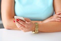 Mano femenina que sostiene un teléfono celular Foto de archivo libre de regalías