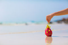 Mano femenina que sostiene una fruta del dragón en fondo del mar Imágenes de archivo libres de regalías