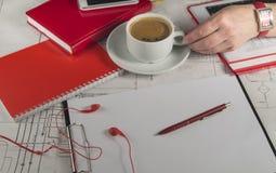 Mano femenina que sostiene una taza de café en la mesa con los dibujos, el cuaderno rojo y el teléfono móvil Imagenes de archivo