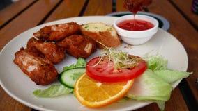 Mano femenina que sumerge las alas de pollo frito en la salsa de tomate, comida malsana sabrosa almacen de metraje de vídeo