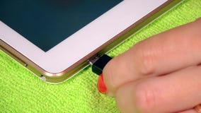 Mano femenina que tapa el cable blanco del usb del micrófono a la tableta elegante almacen de metraje de vídeo